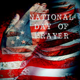 Man praying and text national day of prayer. A double exposure of the flag of the United States and a the hands of a young caucasian man praying, and the text stock photography