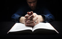 Man praying to God. With his hands resting on a bible Stock Image