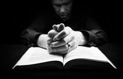 Man praying. To God with his hands resting on a bible stock images