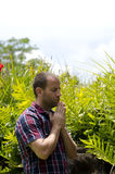 Man praying. In a tropical environment with hands together wearing a plaid shirt Royalty Free Stock Image