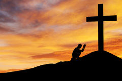 Man praying under the cross. Christian background: Silhouette of man praying under the cross at sunset or sunrise stock photography