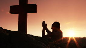 Man praying under the cross. Silhouette of man praying under the cross at sunset/sunsrise stock video