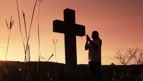 Man praying under the cross. Silhouette of man praying under the cross at sunset/sunsrise stock video