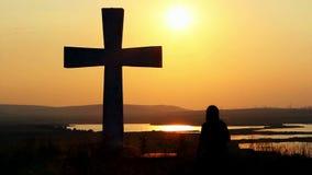 Man praying under the cross. Silhouette of man praying under the cross at sunset/sunsrise stock video footage