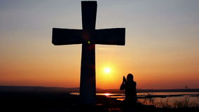 Man praying under the cross. Silhouette of man praying under the cross at sunset/sunsrise stock footage