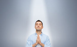Man praying under ray of ligh. Faith in god, religion and people concept - happy man with closed eyes praying under ray of ligh over gray background royalty free stock photos