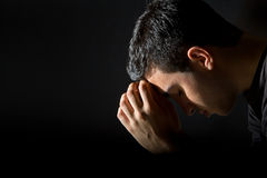 Man Praying. Young man praying in the dark Stock Photo