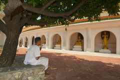 Man prays outside of the temple in Nakhom Pathom, Thailand. Stock Photos