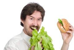 Man prefers salad instead of hamburger Royalty Free Stock Images