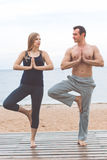Man and pregnant girl are doing yoga on the beach Stock Photos