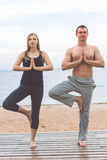Man and pregnant girl are doing yoga on the beach Royalty Free Stock Photography