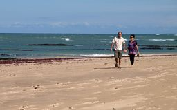 Man and pregnant wife. Walking on the beach holding hands Stock Images