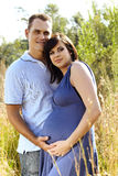 Man and pregnant wife in field. Man and his pregnant wife in blue dress utdoors in field with long grass holding hands on stomach stock photos
