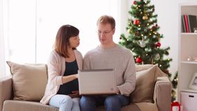 Man and pregnant wife with laptop at christmas stock footage