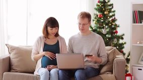 Man and pregnant wife shopping online at christmas stock video footage