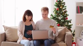 Man and pregnant wife shopping online at christmas stock footage