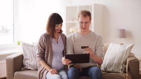 Man and pregnant wife shopping online at home stock video footage