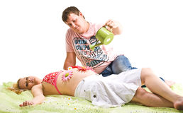 Man and pregnant woman. A man sits on sand, holding a watering can over his pregnant wife's stomach, on which flowers have been placed Royalty Free Stock Image