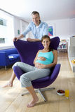 Man by pregnant woman in armchair, smiling, portrait, Royalty Free Stock Photo