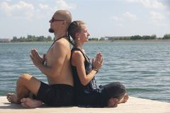 Man and pregnant woman are doing yoga on the beach royalty free stock photography
