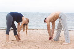 Man and pregnant woman are doing yoga on the beach Royalty Free Stock Photos