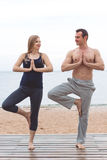 Man and pregnant woman are doing yoga on the beach Stock Photos
