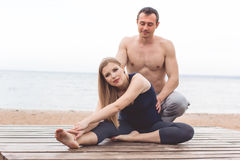 Man and pregnant woman are doing yoga on the beach Royalty Free Stock Image