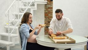 Man and pregnant woman eating pizza at home in their kitchen. Fatty foods. Man and pregnant woman eating pizza at home in their kitchen stock footage