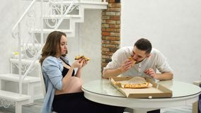 Man and pregnant woman eating pizza at home in their kitchen. Laughter fun. Man and pregnant woman eating pizza at home in their kitchen stock footage