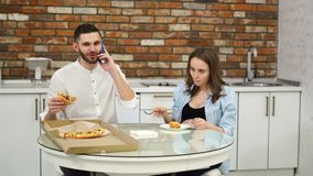Man and pregnant woman eating pizza at home in their kitchen. Man talking on the phone during dinner. Man and pregnant woman eating pizza at home in their stock video footage