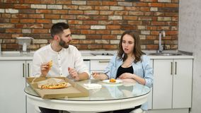 Man and pregnant woman eating pizza at home in their kitchen. Poor diet. Fatty foods. Obesity. Man and pregnant woman eating pizza at home in their kitchen stock video