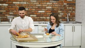 Man and pregnant woman eating pizza at home in their kitchen. Poor diet. Fatty foods. Obesity. Man and pregnant woman eating pizza at home in their kitchen stock video footage