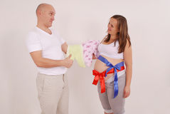 Man and pregnant woman holding baby clothes Stock Images