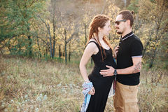 Man and pregnant woman hugging holding hands on the background of wild nature, autumn. love story. Man in a black T-shirt and a pregnant women in a black dress Royalty Free Stock Photo