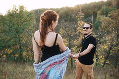 Man and pregnant woman hugging holding hands on the background of wild nature, autumn. love story. Man in a black T-shirt and a pregnant women in a black dress Stock Images