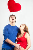 Man and pregnant woman looking up at red heart Stock Photos