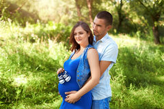 Man and pregnant woman in the park. The family. Stock Photo