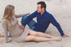 Man and pregnant woman are resting on the beach Stock Photography