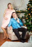 Man and pregnant woman standing near christmas tree. Young men and pregnant women standing near christmas tree Stock Photo
