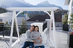 Man and pregnant woman touching her belly in balcony Royalty Free Stock Photography