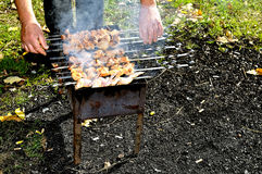 Man prepare meat on fire. (shish kebab Royalty Free Stock Photos