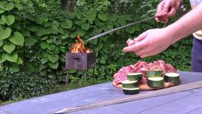 Man prepare shashlik zucchini on skewer. Grill fire in garden. stock footage
