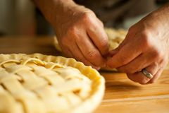 A man prepares apple pies. A man`s hands preparing the crimped pastry crusts of two unbaked apple pies. Horizontal image with shallow depth of field stock images