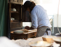 Man prepares the dough for baking bread. Man puts the dough on a shovel for bread stock photography