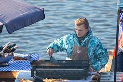 Man prepares food at the popular farmers market at the Naplavka. PRAGUE, CZECH REPUBLIC - NOVEMBER 17, 2018: Man prepares foood at the popular farmers market at royalty free stock images