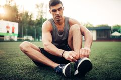 Man prepares for outdoor fitness workout. Sportsman sitting on the grass and tying shoelaces on sneakers Royalty Free Stock Photography