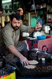 Man prepares Pakistani chapli kebab meat dish on skillet Gilgit Pakistan Royalty Free Stock Image