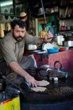 Man prepares Pakistani chapli kebab meat dish on skillet Gilgit Pakistan Stock Photo