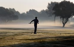 Golf and morning fog. A man prepares to hit the ball on a foggy morning during a companies golf tournament in the spanish island of mallorca Royalty Free Stock Images