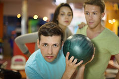 Man prepares to throw of ball; man and woman look Stock Photography